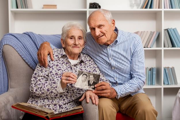 Очаровательны зрелый мужчина и женщина, держащая свадебное изображение