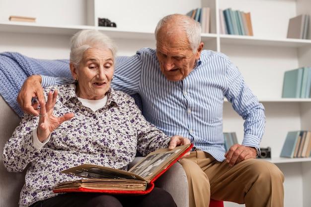 フォトアルバムと年配のカップルの肖像画