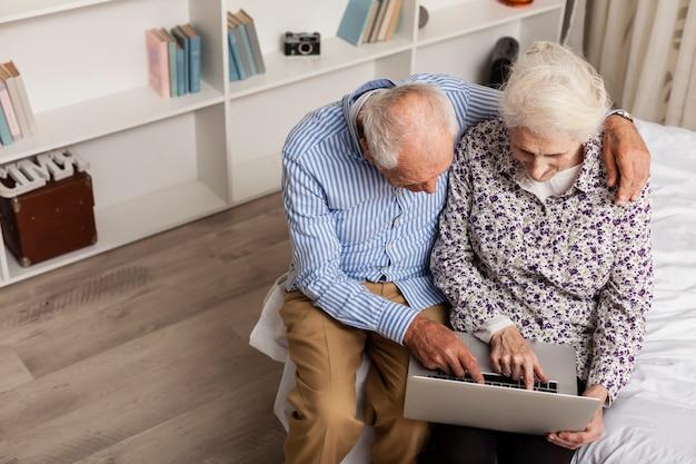 Пожилой мужчина и женщина, используя ноутбук