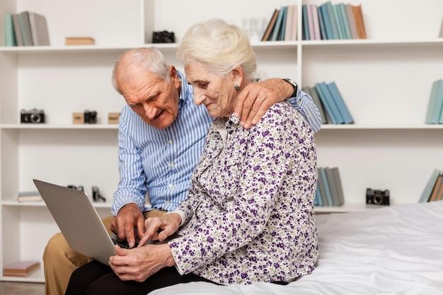 Прекрасный старший мужчина и женщина, используя ноутбук