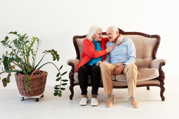 Пожилой мужчина и женщина, сидя на диване