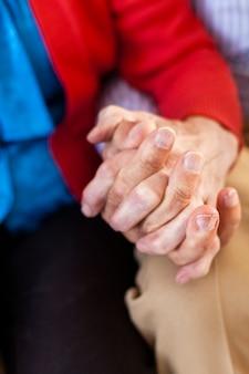 Крупным планом пожилые супружеские пары, взявшись за руки