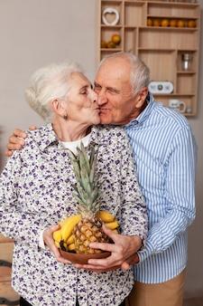 Очаровательны старший мужчина и женщина целуются