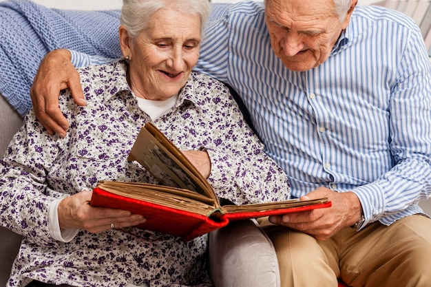 Пожилая пара смотрит в фотоальбом