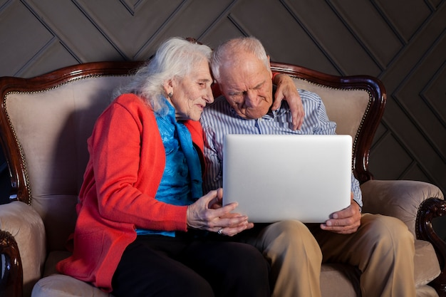 Прекрасный старший мужчина и женщина, держащая ноутбук