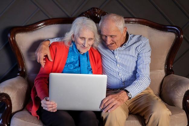 Пожилая пара держит ноутбук вместе