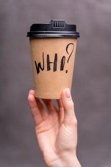 コーヒーカップを保持しているクローズアップの女の子