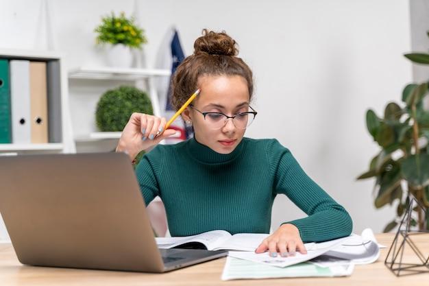 Средний снимок девушка сосредоточена на учебе