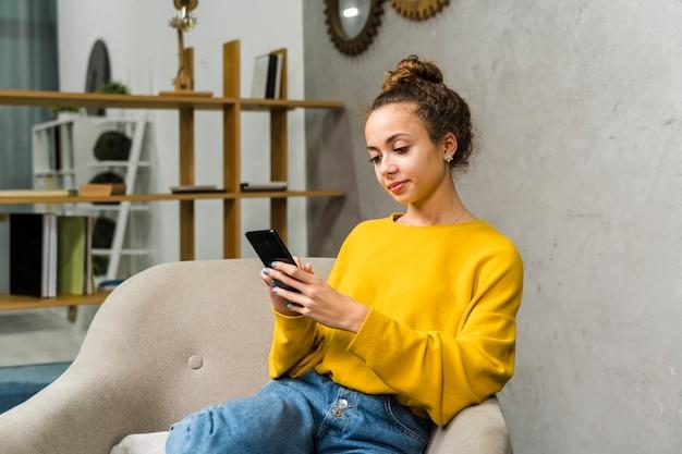黄色いセーターとスマートフォンでミディアムショットの女の子