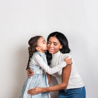 Дочь целует маму в щеку