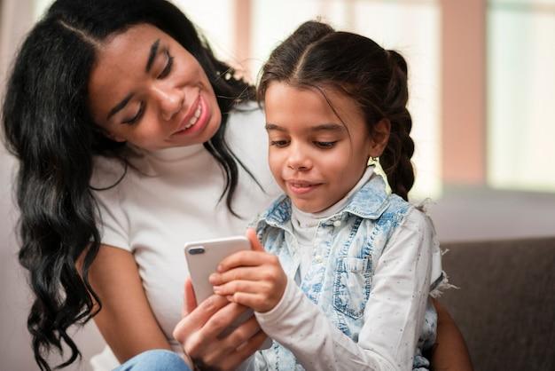 電話を使用する子供を教えるママ