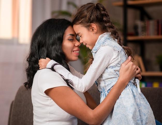 Вид сбоку мать и дочь обнимаются