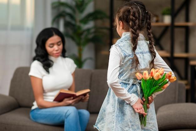 花を持つお母さんを驚く女の子