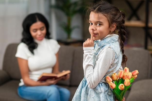花を持つお母さんを驚くべき少女