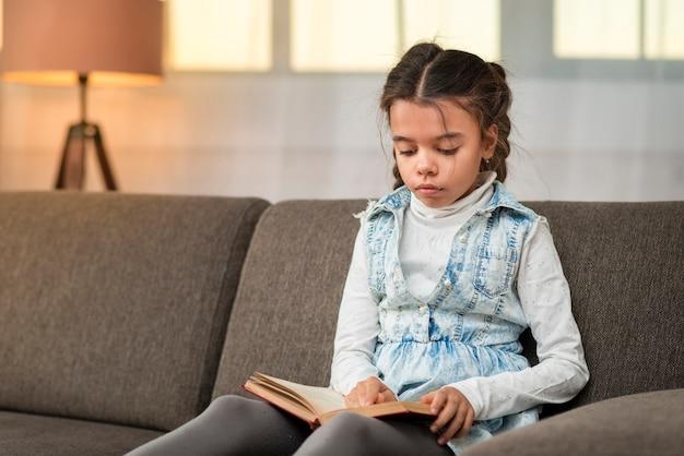 Маленькая девочка на диване рассказывает истории
