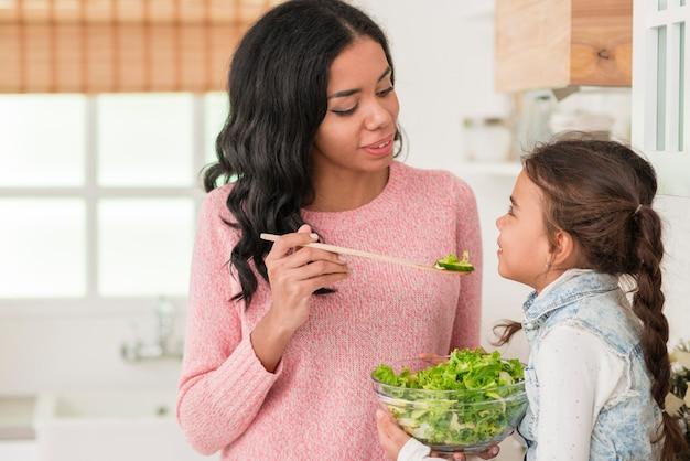 母は彼女の娘のサラダを給餌