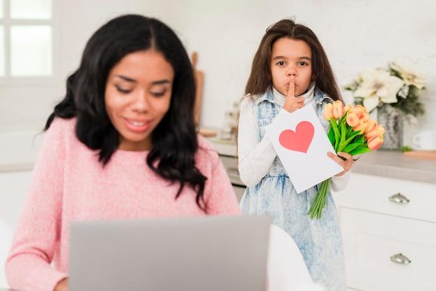 Милая девушка удивляет свою маму во время работы