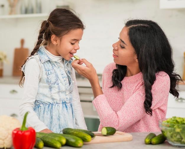 Мама кормит дочку овощами