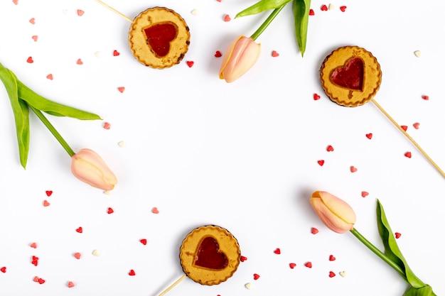 バレンタインデーのためのチューリップとクッキーのフラットレイアウト