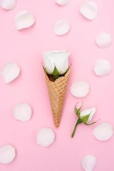バラと花びらのアイスクリームコーンのフラットレイアウト