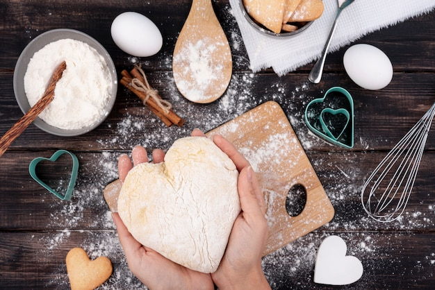 Руки держат тесто в форме сердца