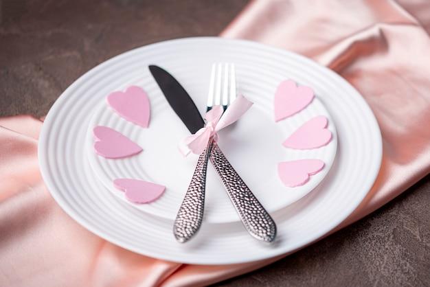 Высокий угол тарелки с сердечками и столовыми приборами