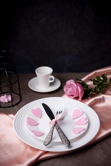 Высокий угол столовых приборов на тарелках с сердечками и копией пространства