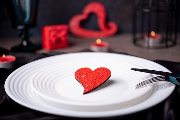 Крупный план сердца на тарелках со столовыми приборами и свечами
