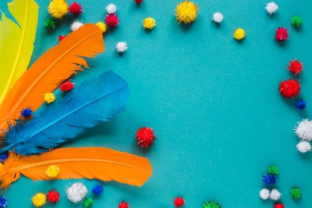 Вид сверху разноцветных перьев и помпонов