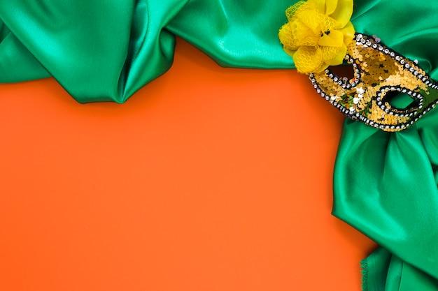 Вид сверху текстиля и маски для карнавала с копией пространства