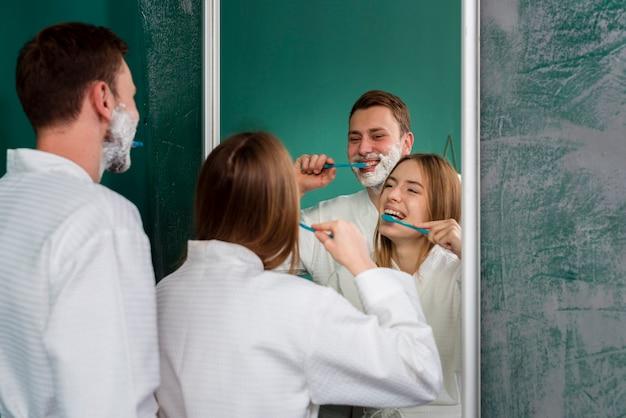 Пара в халатах чистит зубы в зеркале