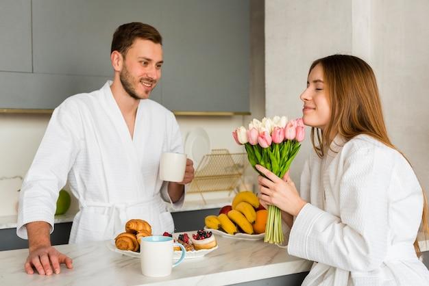Пара в халатах на кухне с букетом тюльпанов