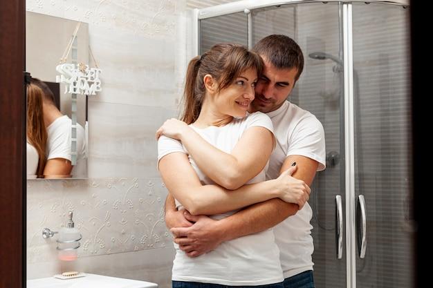 Вид спереди молодая пара, охватывающей в ванной комнате