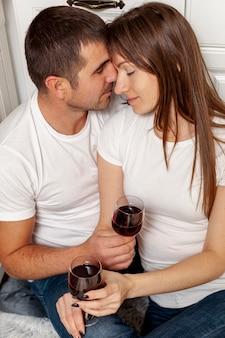 ワインのグラスを保持している若いカップル