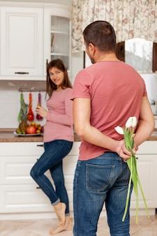 Осторожный мужчина приносит цветы своей жене