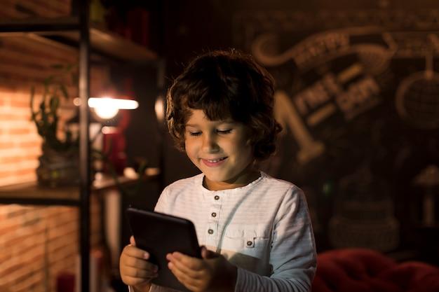 彼のタブレットで遊ぶ少年