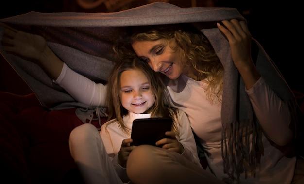 毛布の後ろに一緒に時間を過ごす正面の母と娘