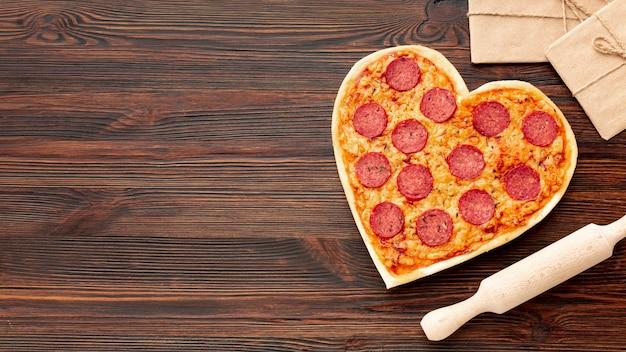 ハート型のピザとコピースペースとのバレンタインデーディナーの素敵なアレンジメント