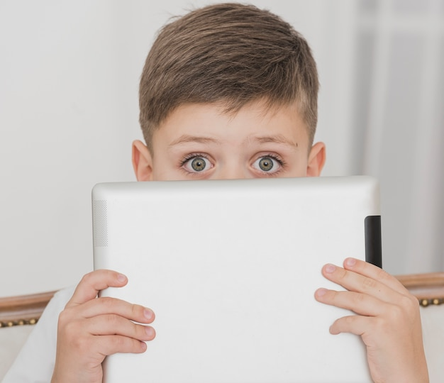 Макро маленький мальчик держит планшет