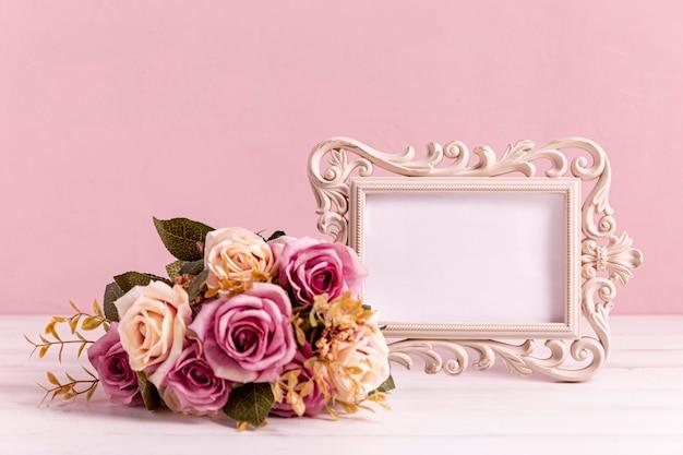 空のフレームとバラの花束