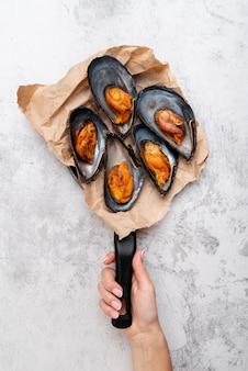 ムール貝とパンを持っている手