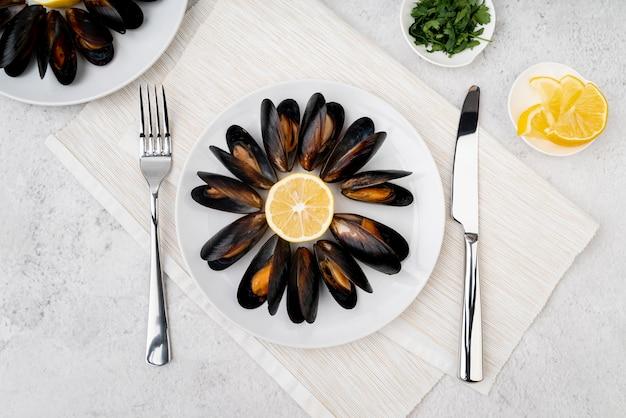 Тарелка вкусных мидий со столовыми приборами