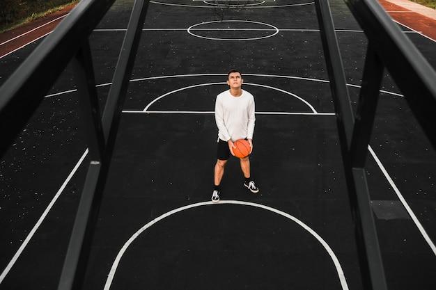 コートのフルショットのバスケットボール選手