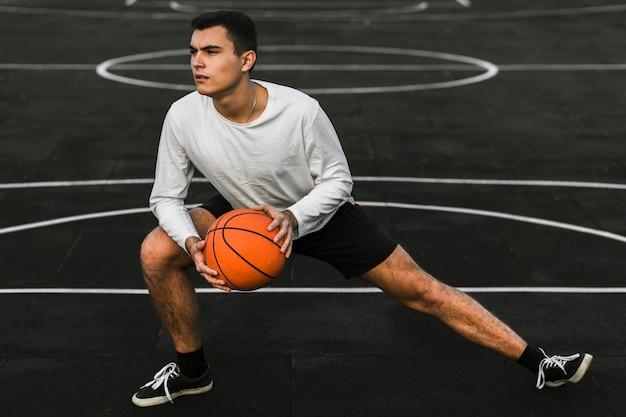 バスケットボールコートでストレッチハンサムな運動選手