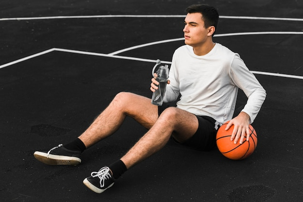 Баскетболист держит бутылку с водой