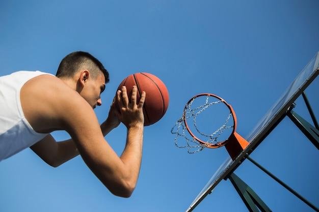 ネットにボールを投げるバスケットボール選手