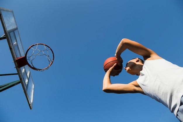 Спортсмен играет в баскетбол под низким углом