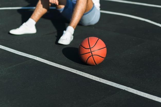 バスケットボールコートの上に座って認識できない選手