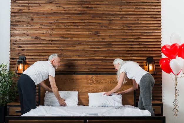 一緒にベッドを作る年配のカップル