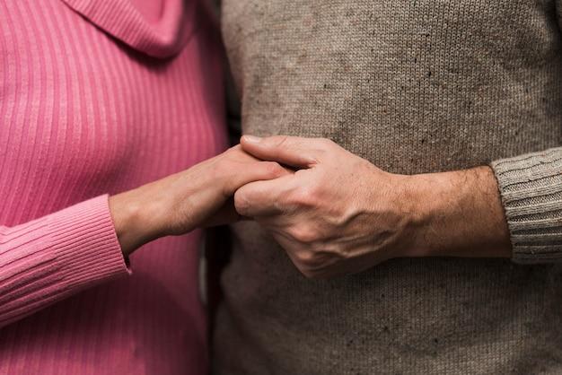 手を繋いでいるクローズアップシニアカップル